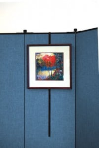 A framed art piece hangs on a metal artwork hanger that hooks over a blue fabric sound absorbing wall