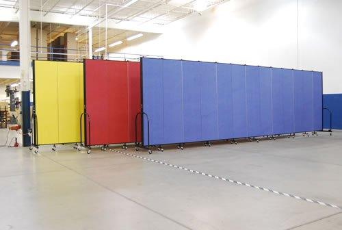 A red, blue and yellow room divider are displayed in a warehouse