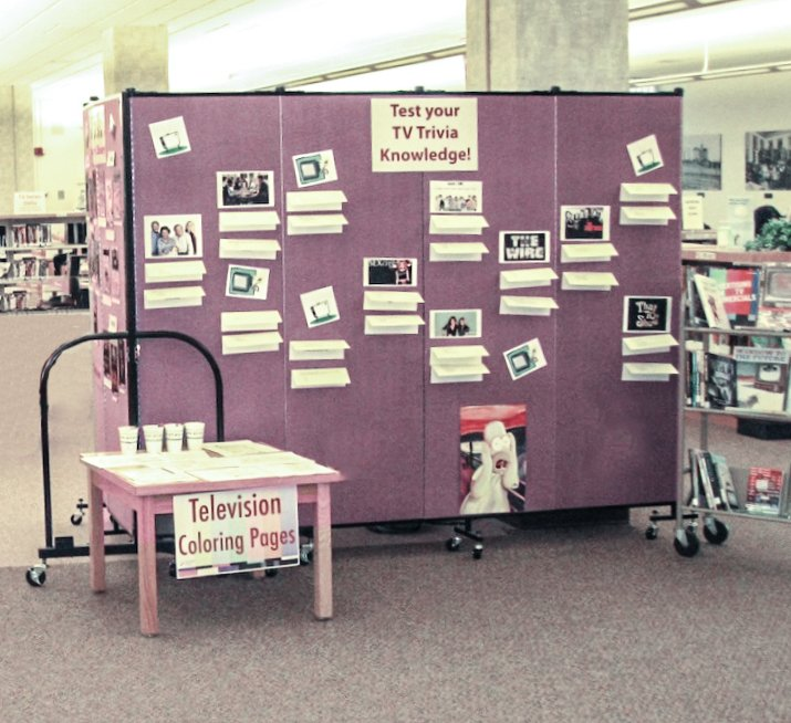 Clues are tacked to a portable wall to create a library TV trivia contest display