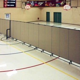 Too hot for outdoor PE class? Screenflex accordion walls are used to divide this gymnatorium. Half is used for PE and half for lunch.