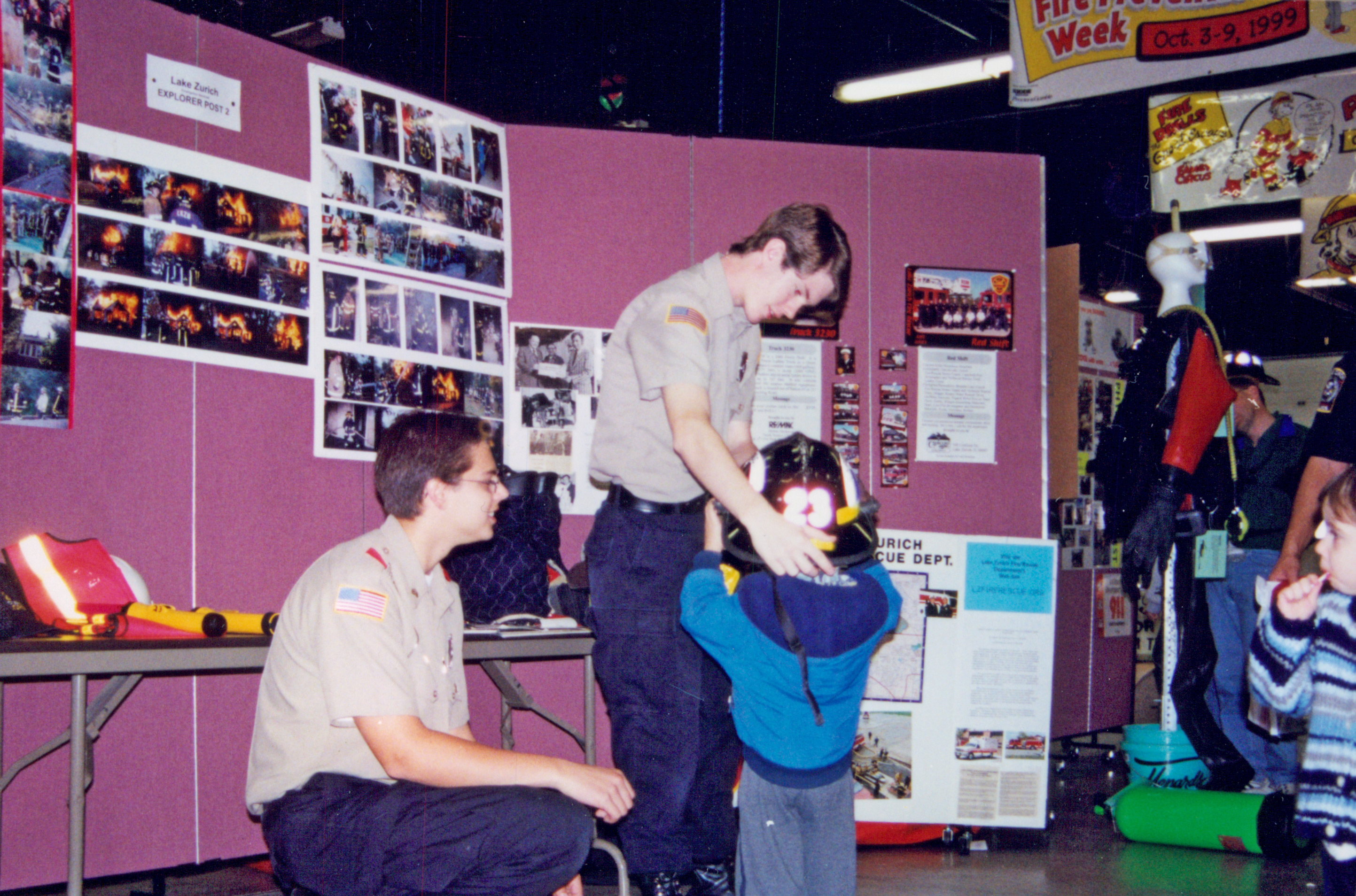 During fire prevention week, the local Boy Scout troop volunteer assisting kids with trying on equipment