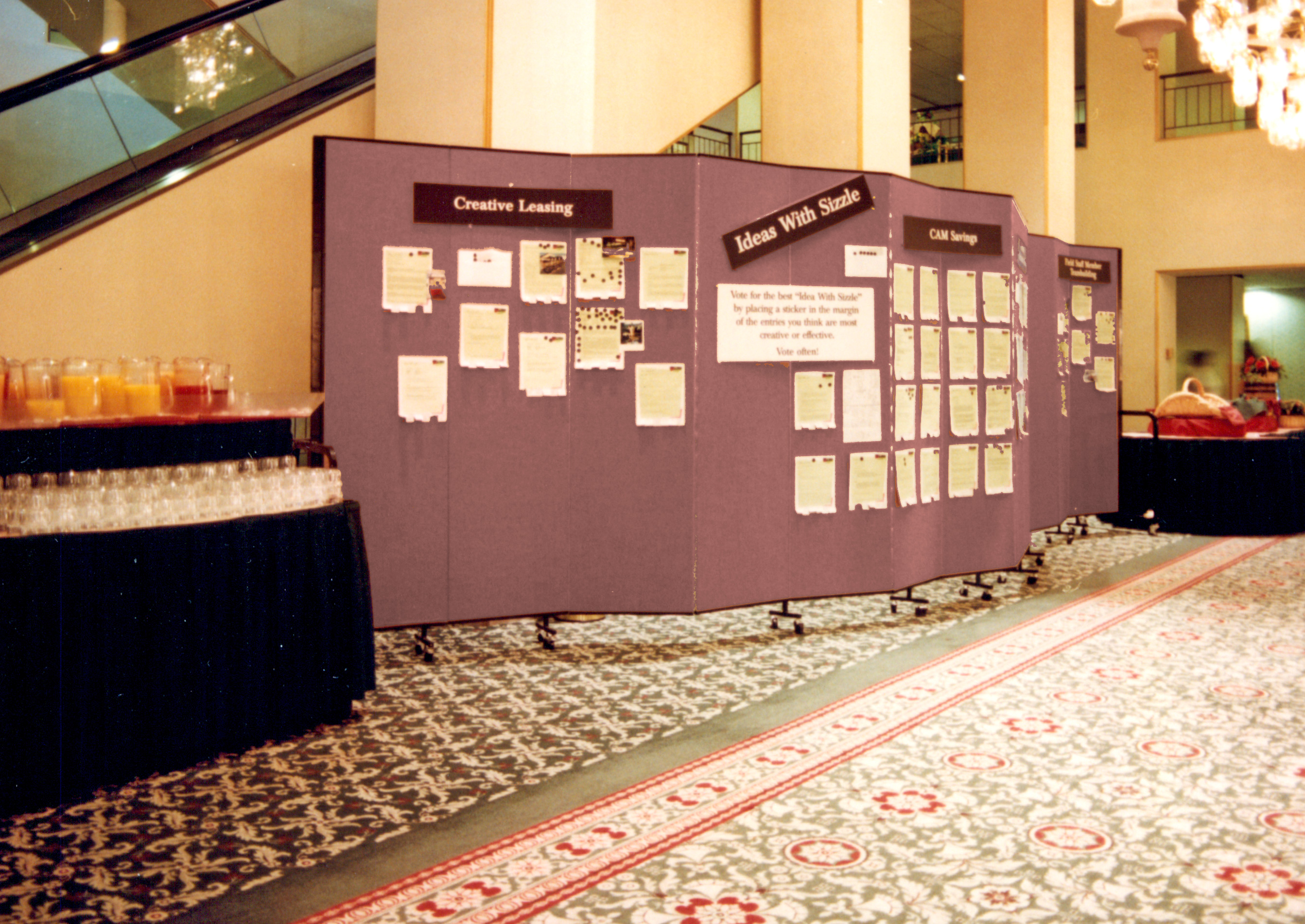 Information for members attending a conference is displayed on portable walls between snack tables