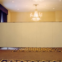A room divider is extended across the back of a ballroom to hide extra supplies