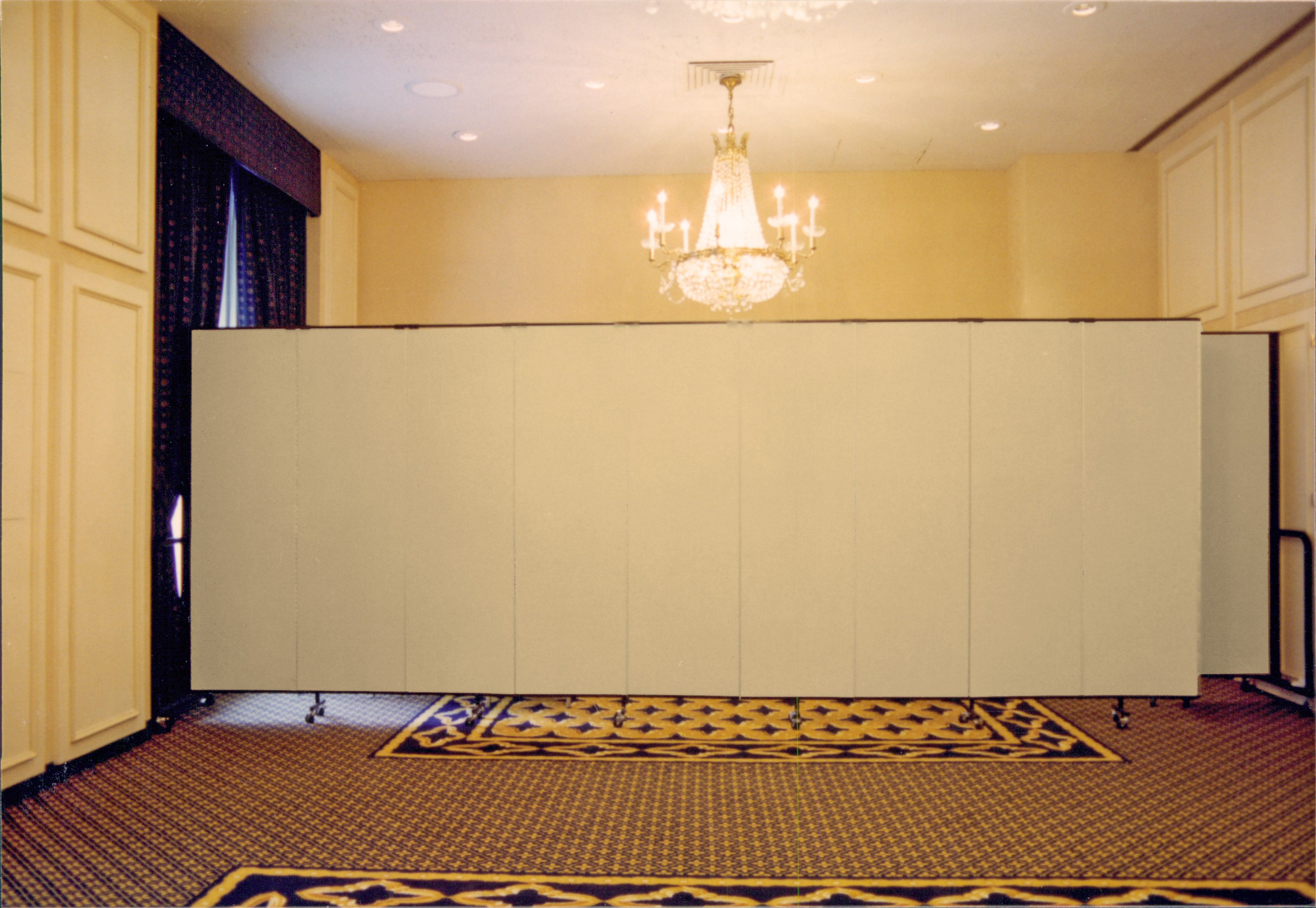 A room divider is opened across the back of a ballroom to hide unused items