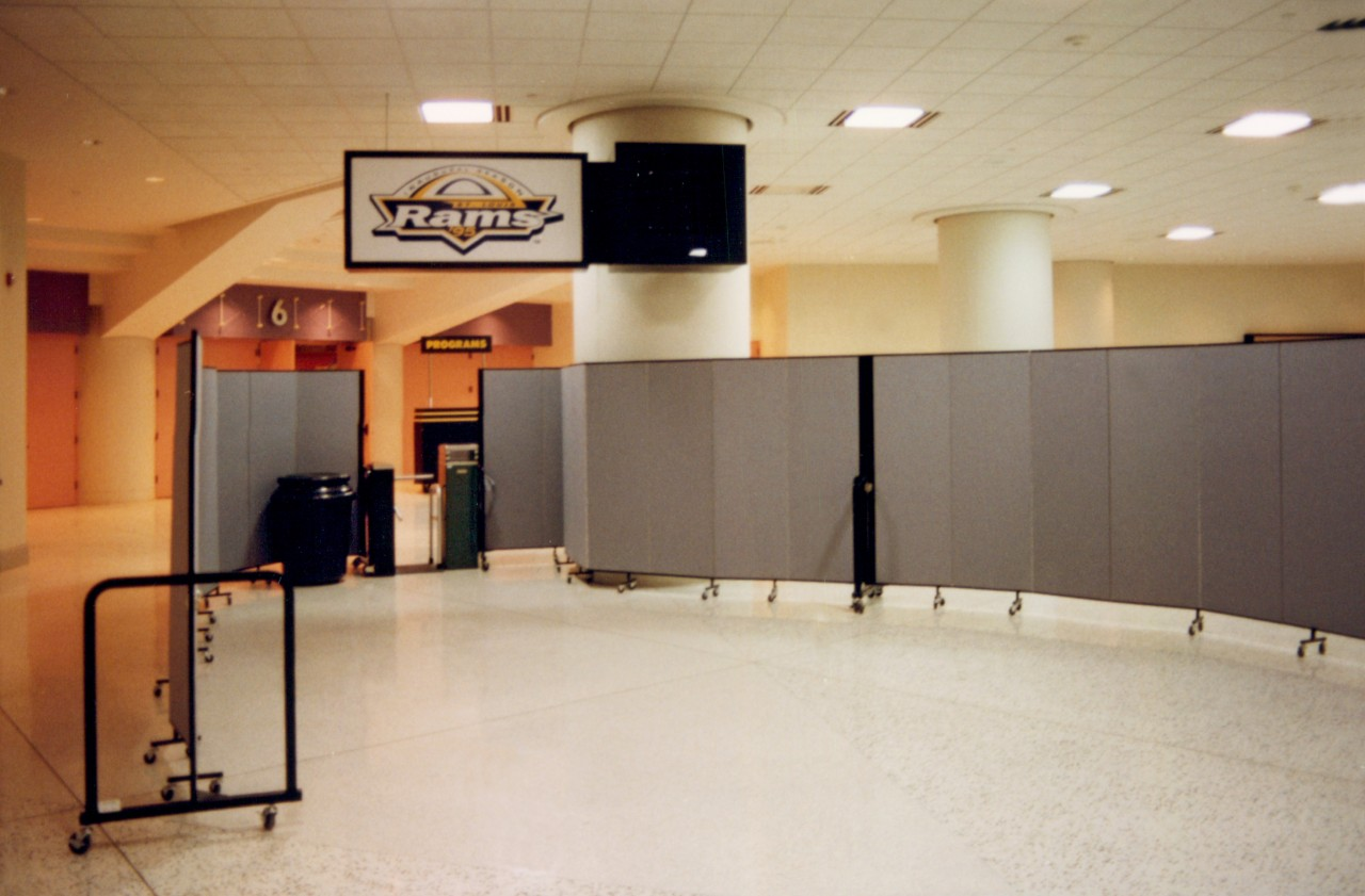 Two room dividers are arranged on each side of a turnstile inside an arena to create a security check point