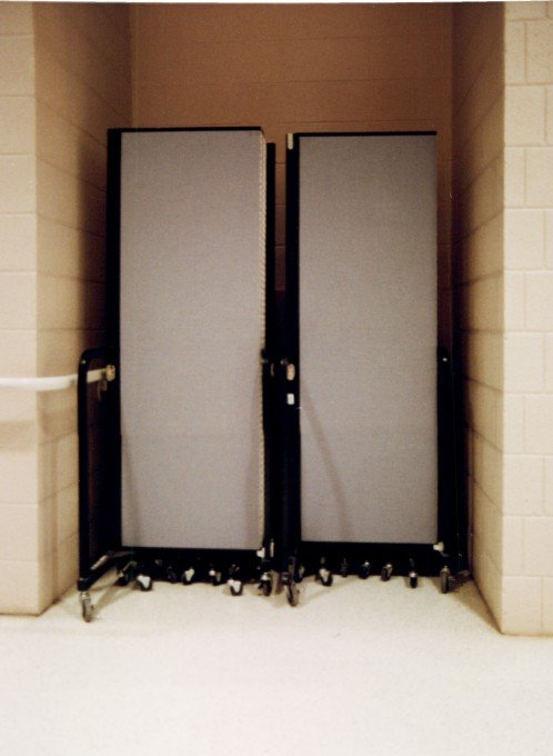 A set of room dividers closed and stored in a wall nook