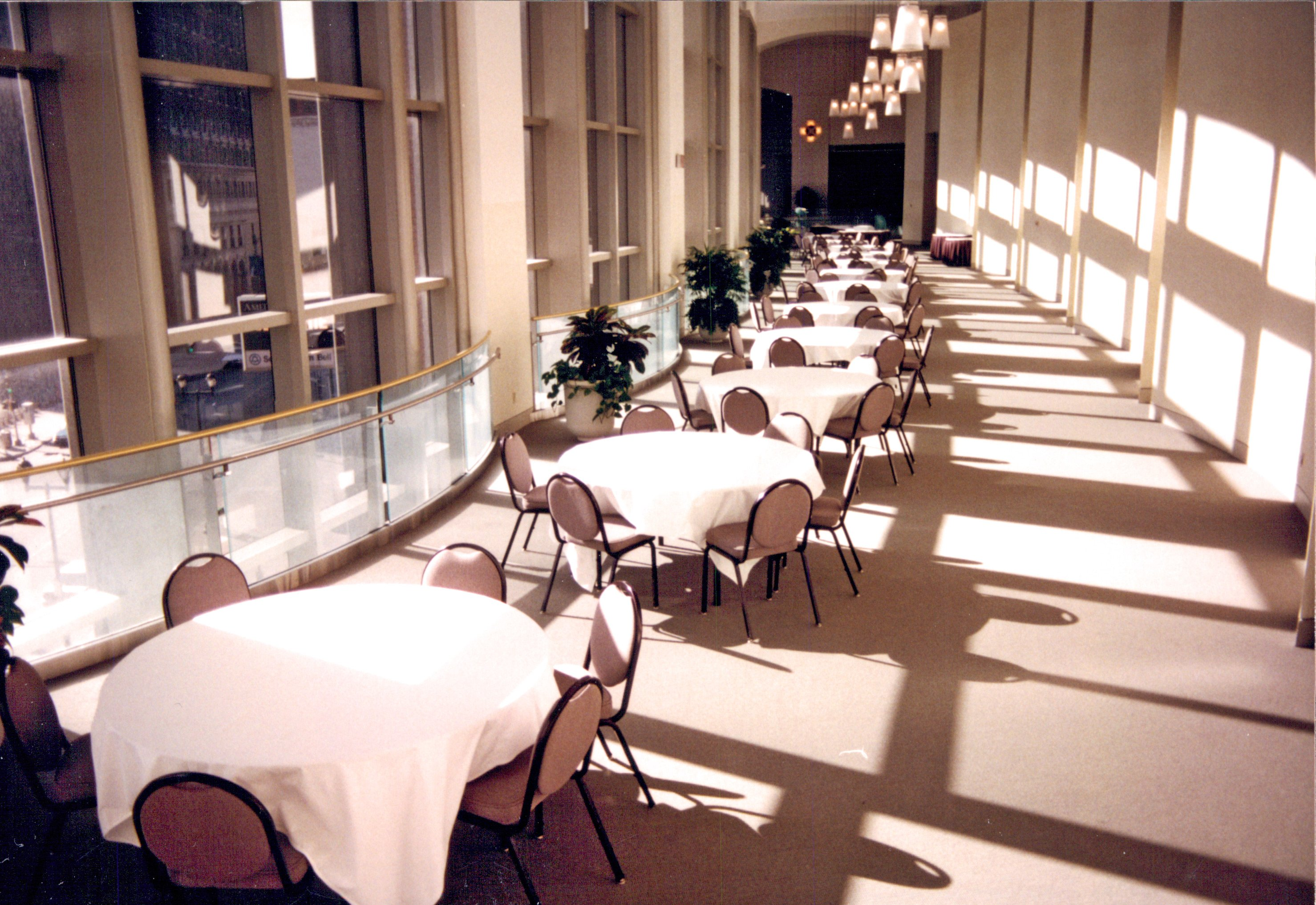 A long row of round banquet tables and chairs lined up next to floor to ceiling windows in a hallway