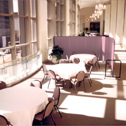 The sun shines onto three round banquet tables and chairs arranged in a banquet hall shielded on one side by a portable room divider