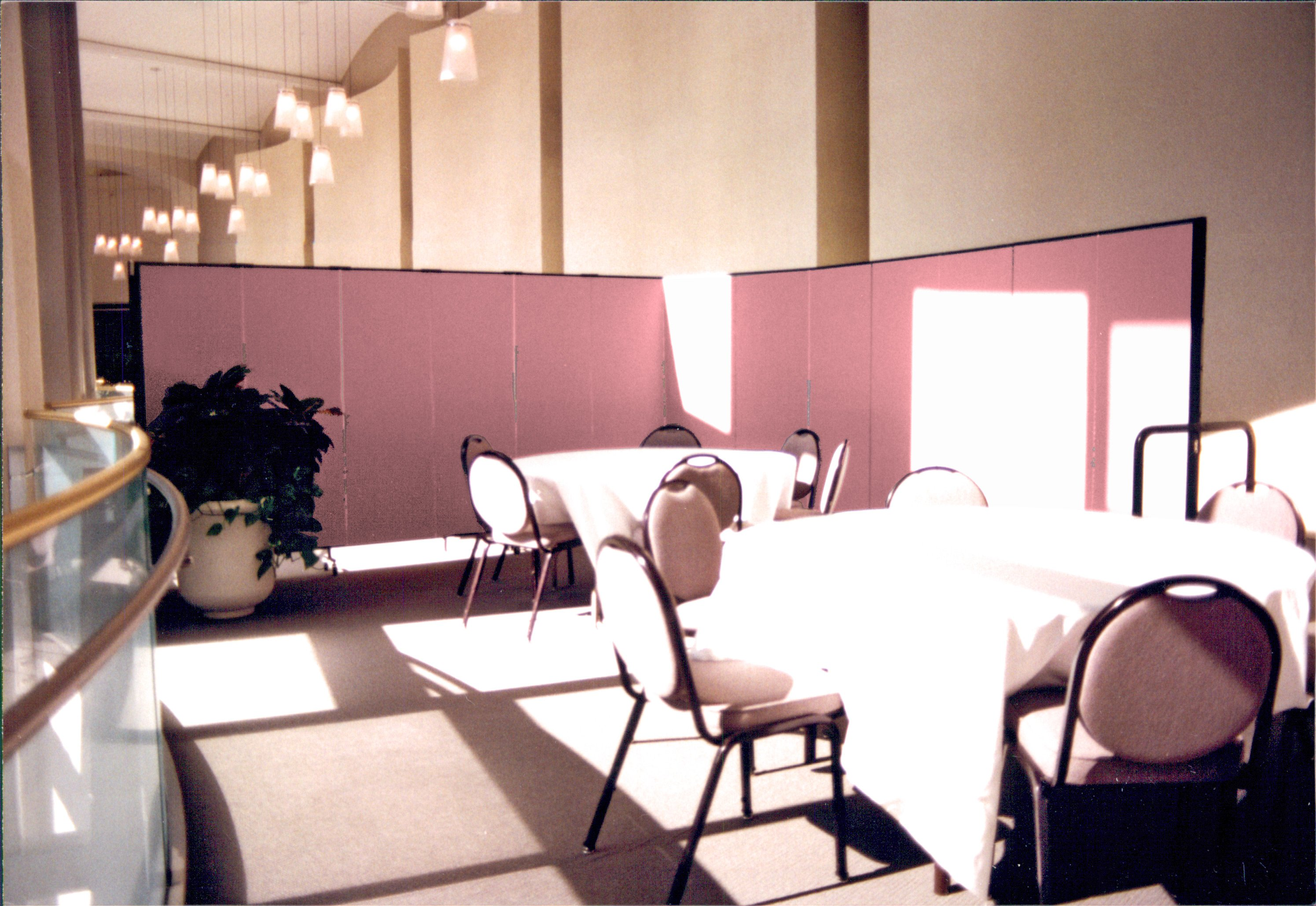 A set of round banquet tables and chairs arranged next to a set of windows and hidden from a hallway by a rolling room divider