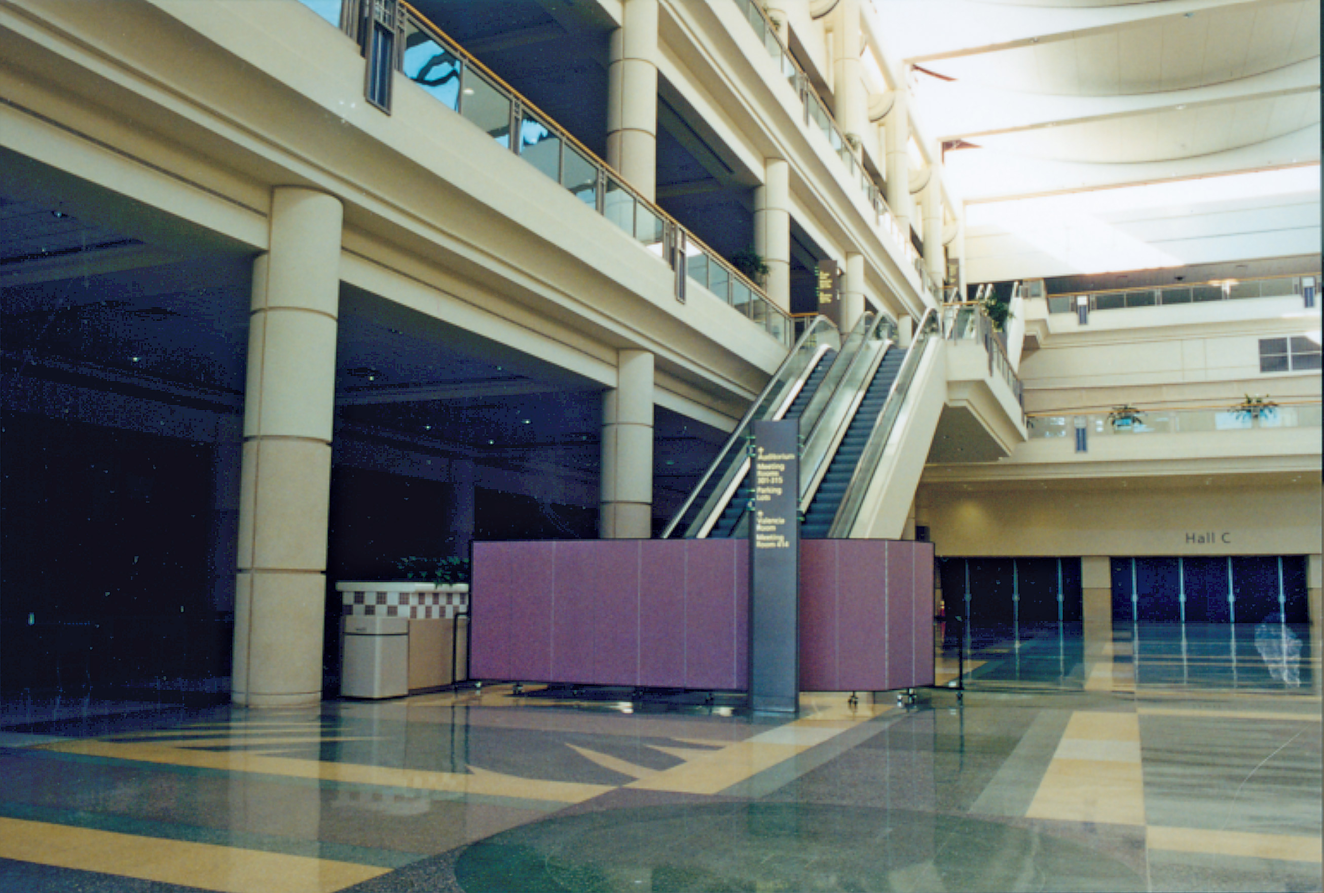 A room divider hides repairs being down on an escalator in a large convention center lobby
