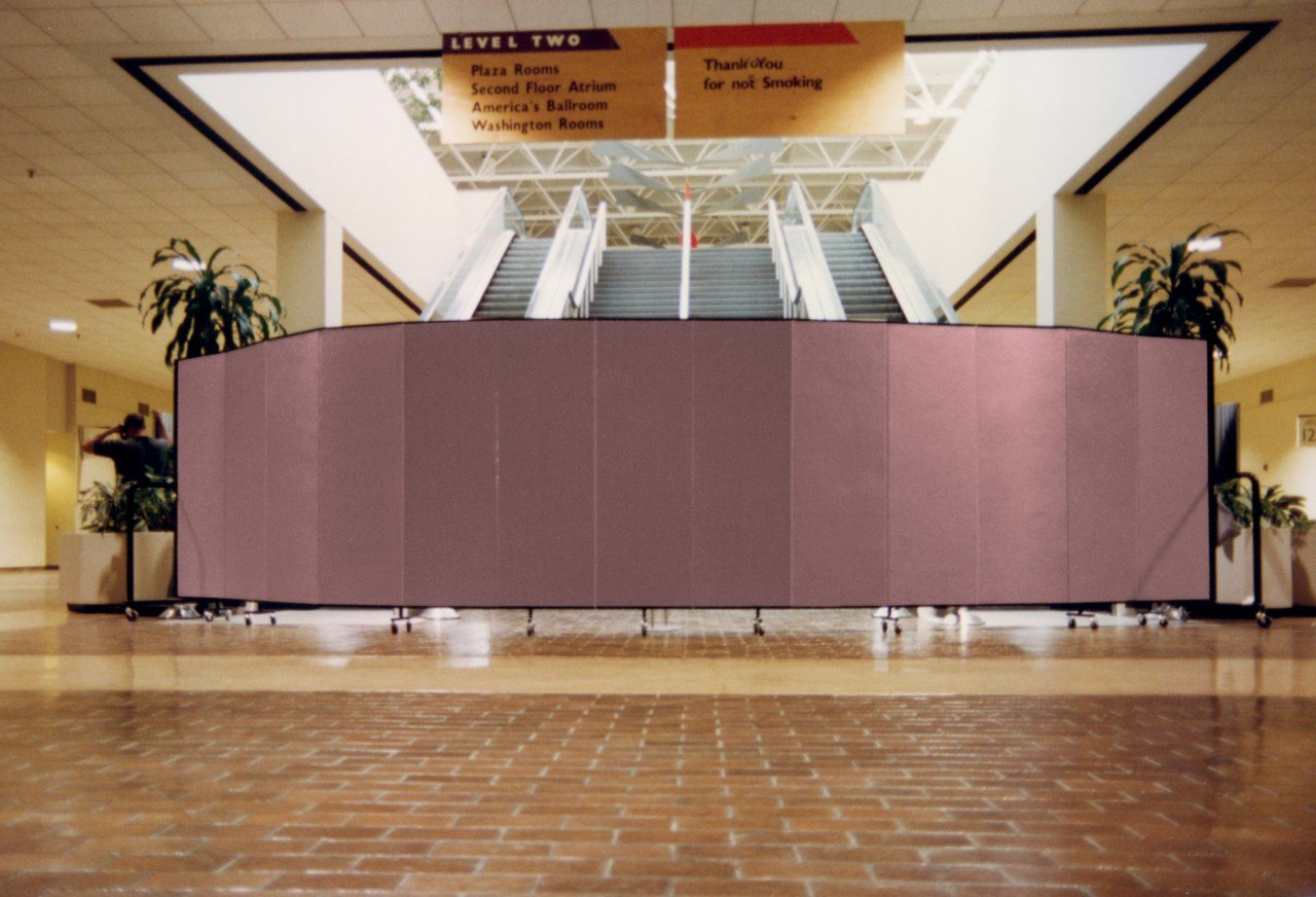A 13 panel room divider arranged in an arch to deny access to a set of stairs and escalators