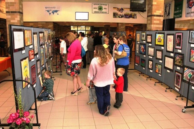 Guests view art tacked to art display panels