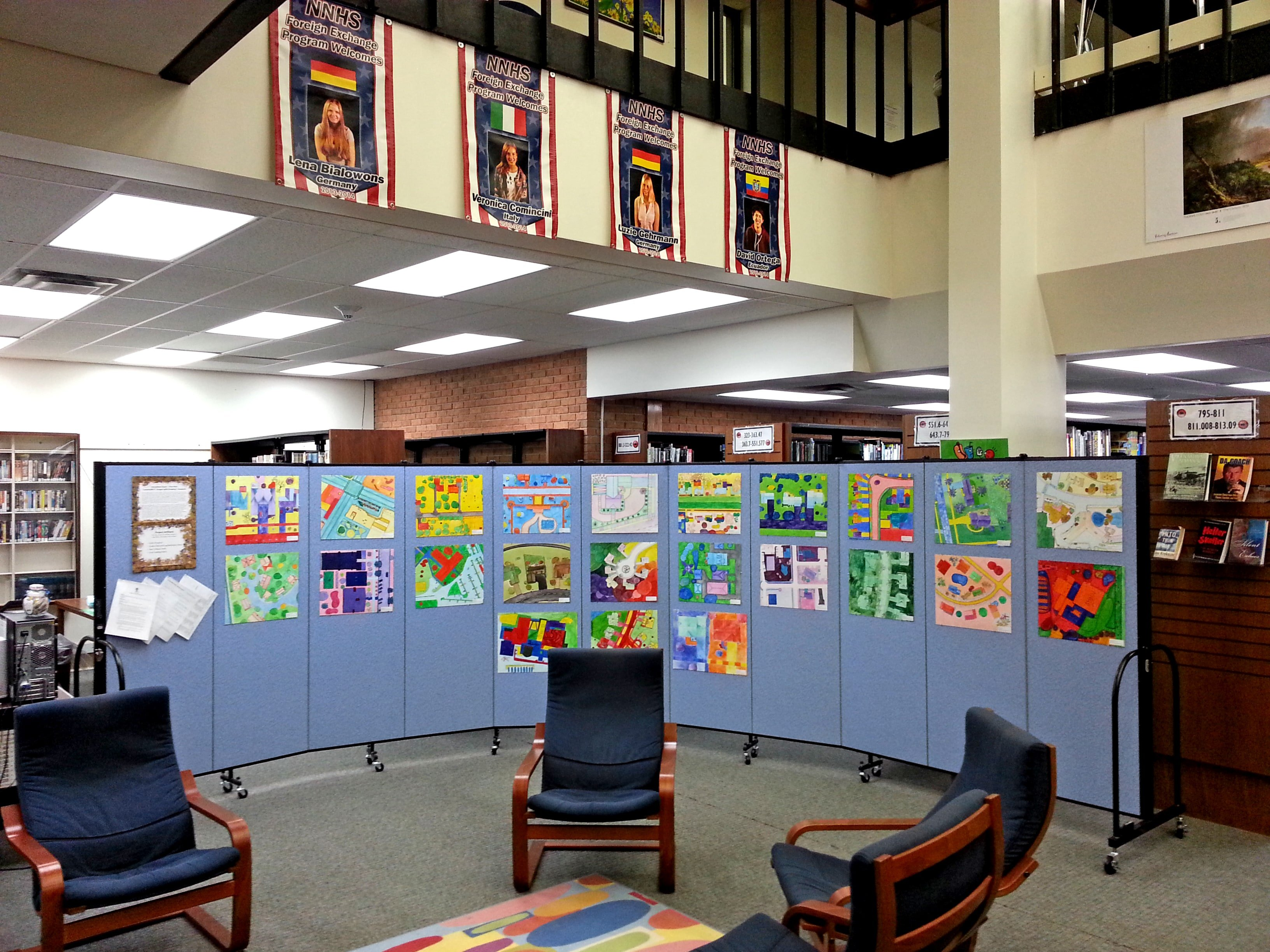 Student artwork displayed on an eleven panel room divider in a school library