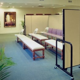 A row of chairs follows two rows of benches in a prayer room that are shielded by a set of room dividers