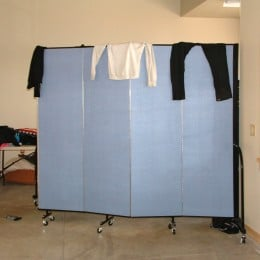 A table of clothes is stored behind a room divider in the corner of a room where clothes are draped over the top of the divider