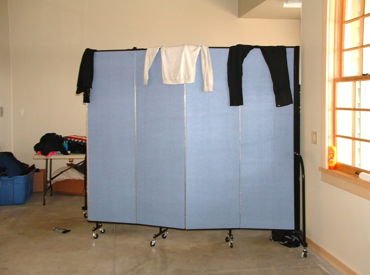 incredible How To Make A Portable Dressing Room Part - 8: A table of clothes is stored behind a room divider in the corner of a room