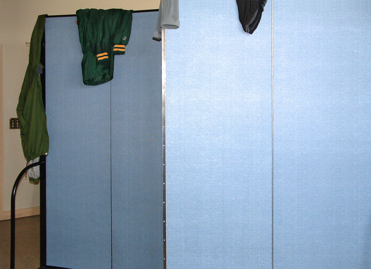Sports coats draped over the top of a blue room divider