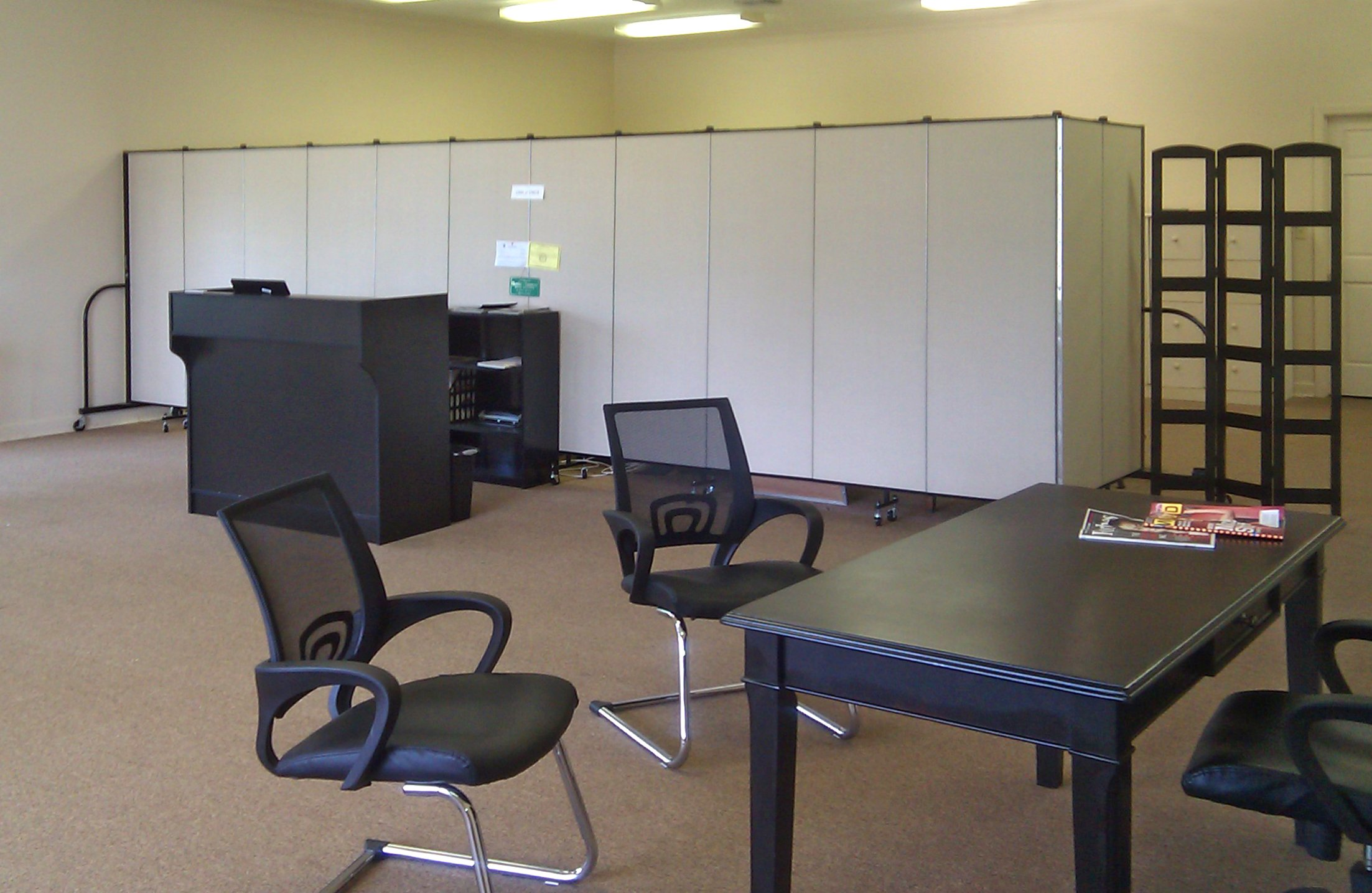 A room divider is used to create private office in the rear of open office space