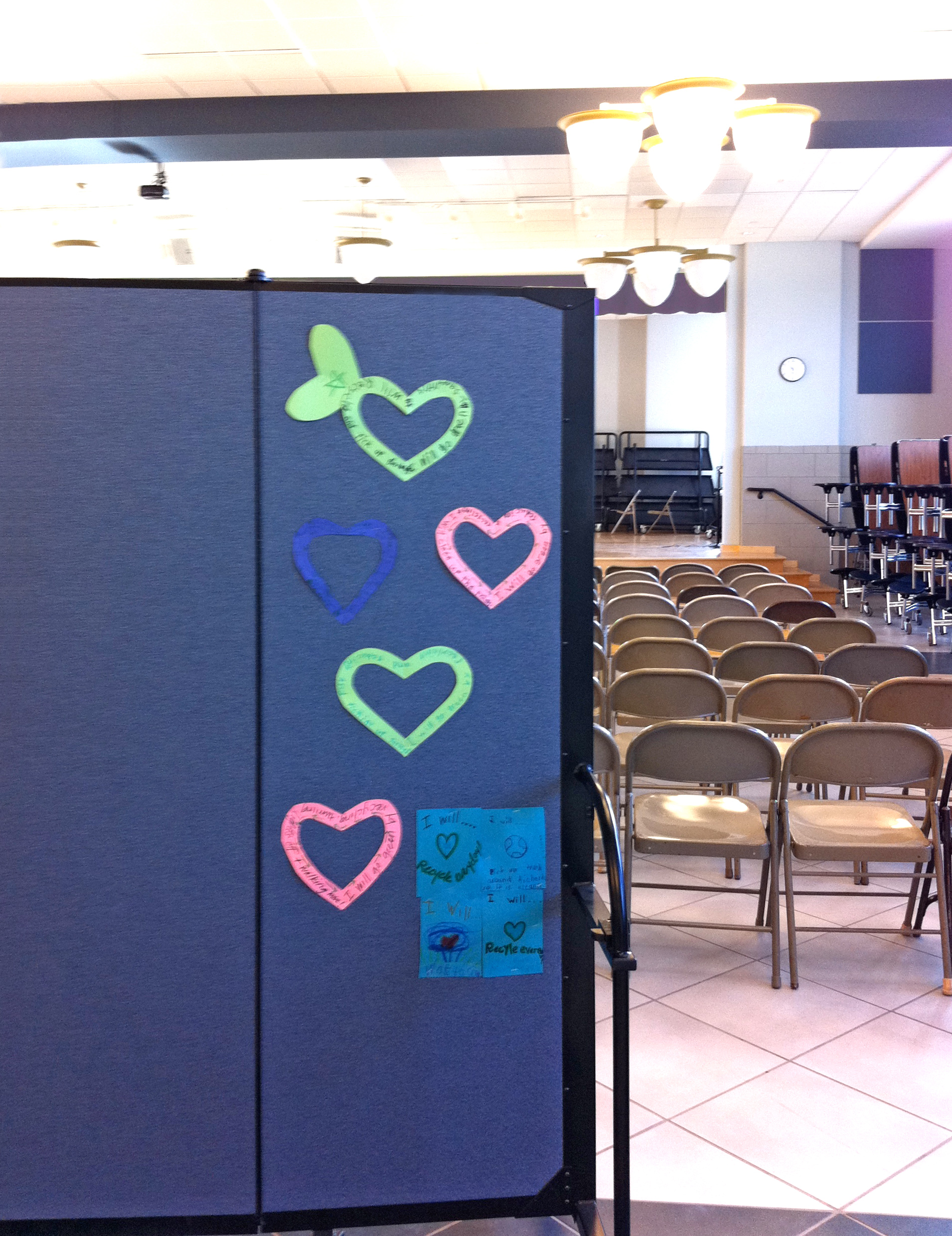 5 decorative hearts tacked to a room divider in the rear of church hall