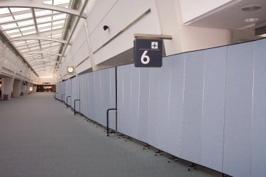 A row of room dividers creates a long wall near gate 6 in an airport terminal