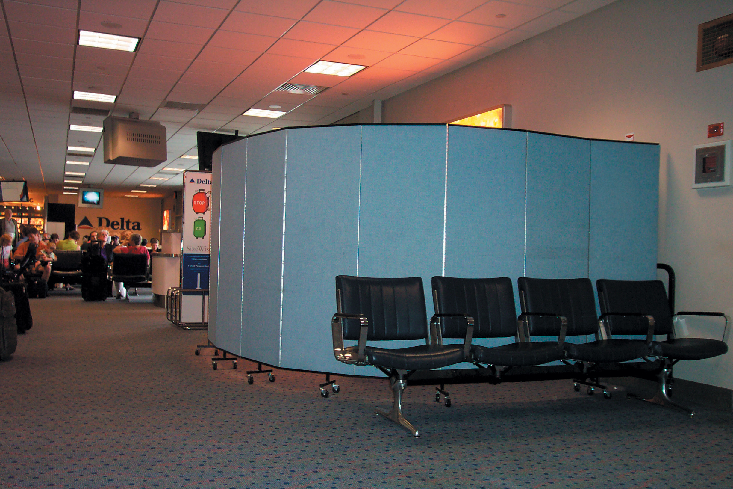 A blue room divider arranged in a half circle hides a screening area in an airport