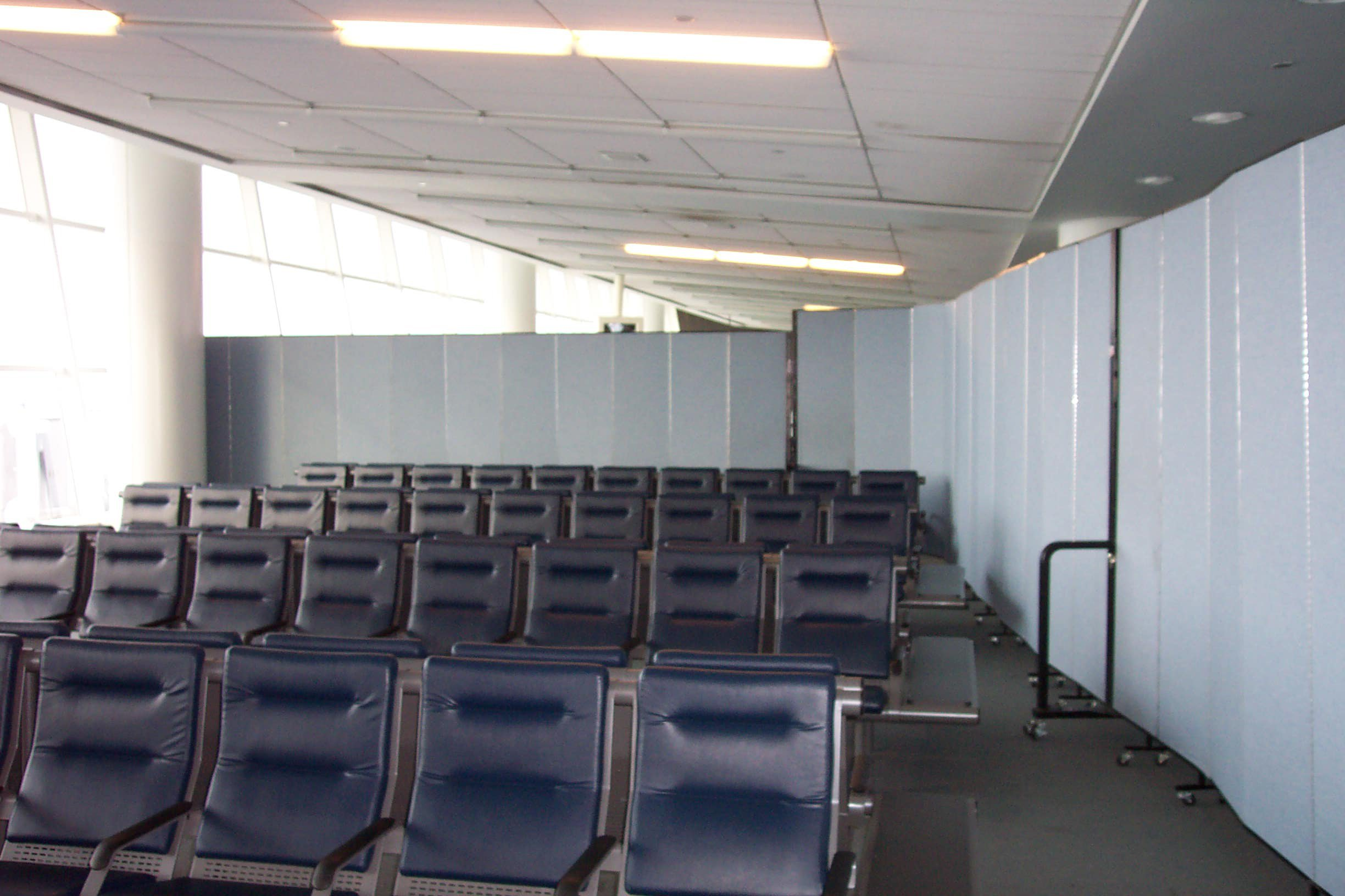 Room dividers surround rows of chairs in an airport waiting area