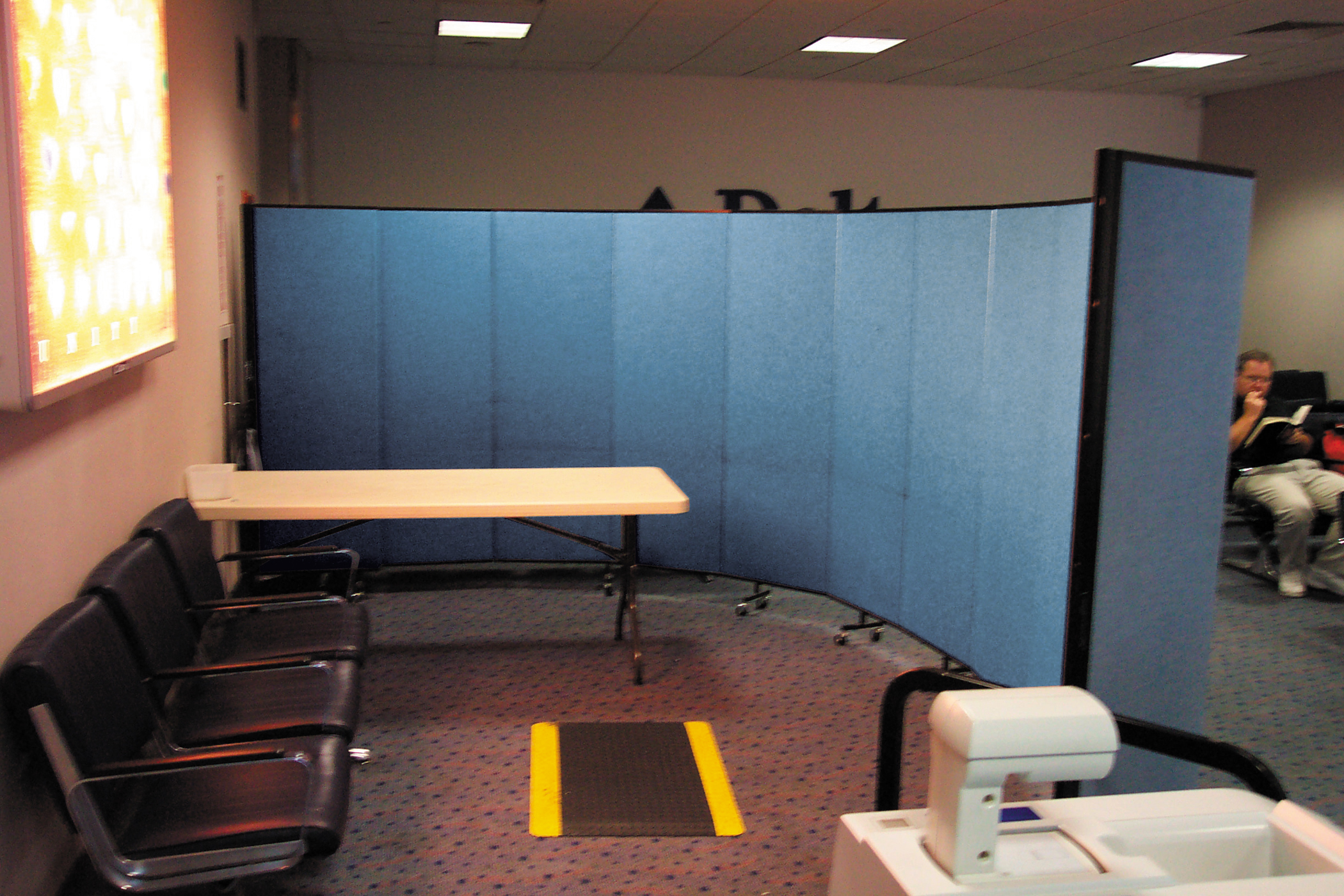 A blue room divider on wheels separates a medical waiting area and a screening room