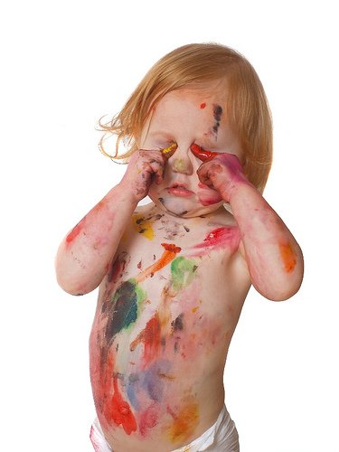 A toddler with paint on its body
