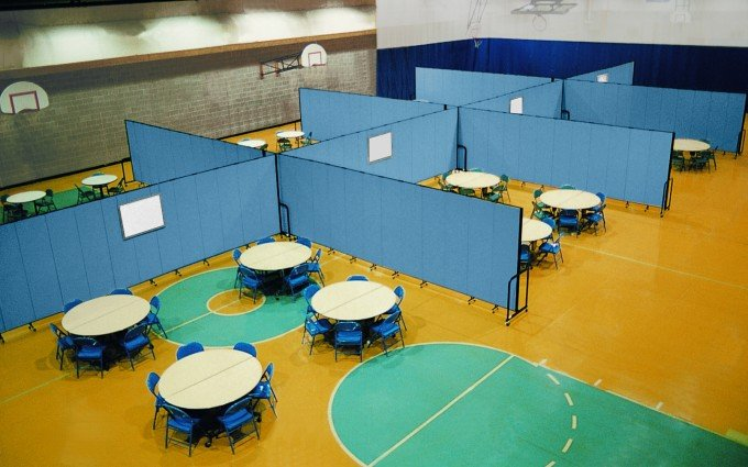 Several blue room dividers are used to divide round tables and chairs in each of the eight classrooms