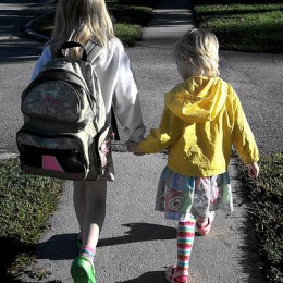 Sisters hold hands as they walk along a sidewalk