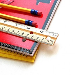 Pencils and a ruler stacked on a folder and spiral notebook