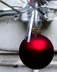 A red ornament hanging amongst a grey background
