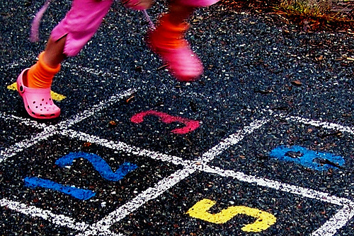 The feet of a young girl playing hopscotch
