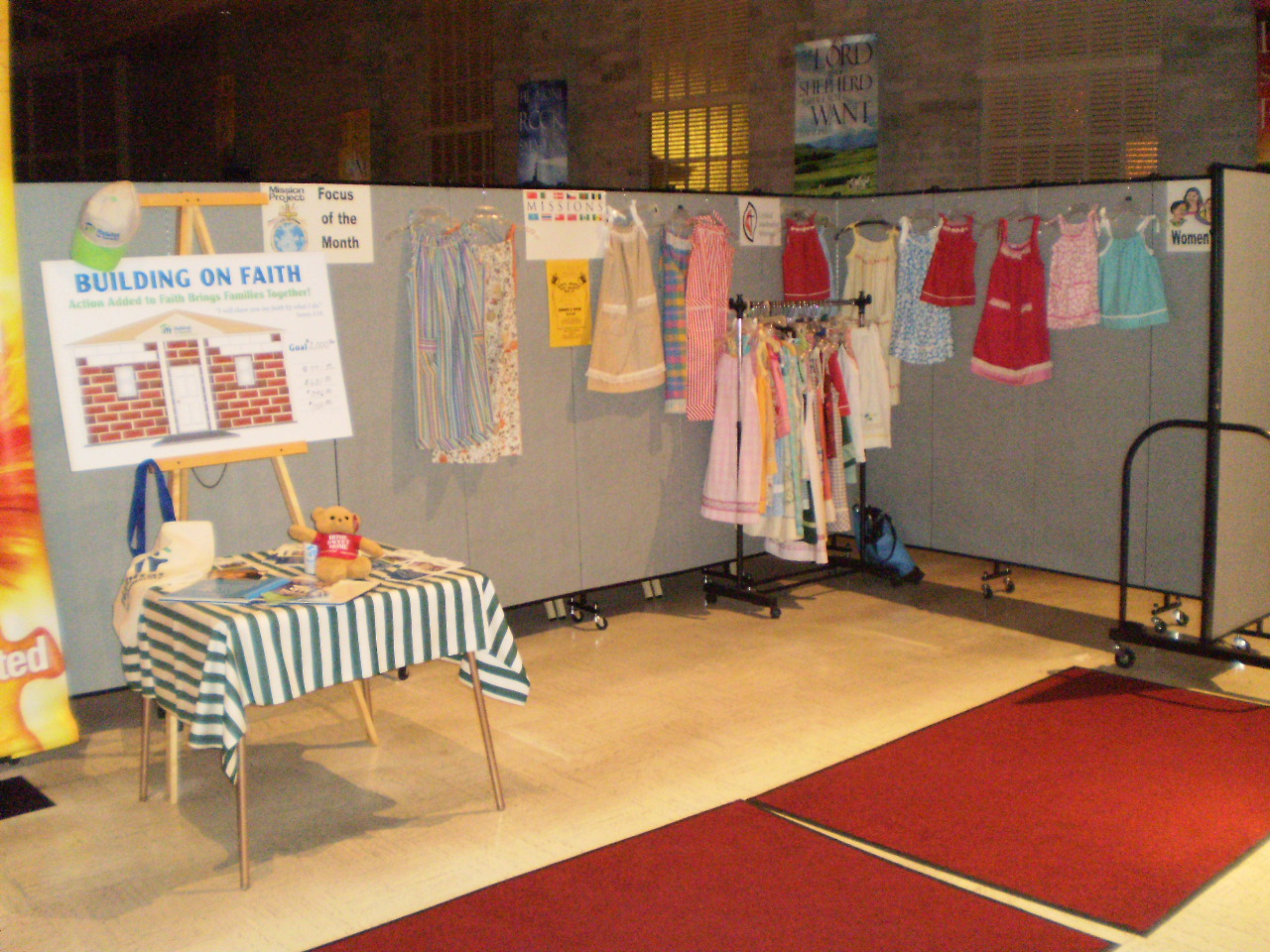 Female dresses are displayed on and around a Screenflex Room Divider in the back of a church entrance