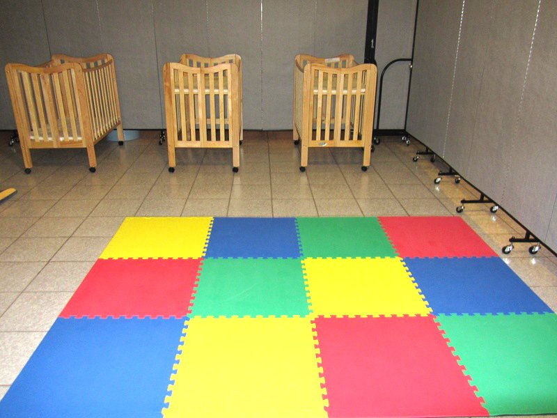 3 cribs lay next to an area of colorful foam square floor tiles arranged for infant play