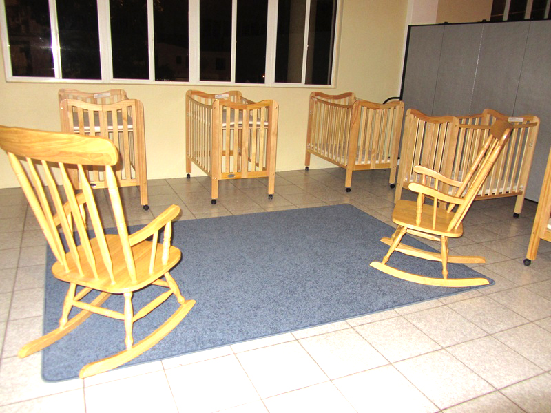 5 cribs and two rocking chairs are separated from a toddler room with room dviders