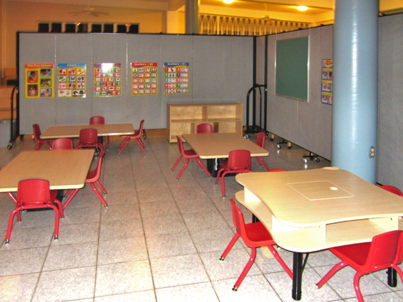 4 short table and chairs are arranged on a tile floor in a preschool room