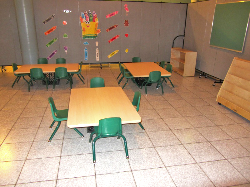 Three short tables and chairs are arranged on a tile floor in a daycare center.
