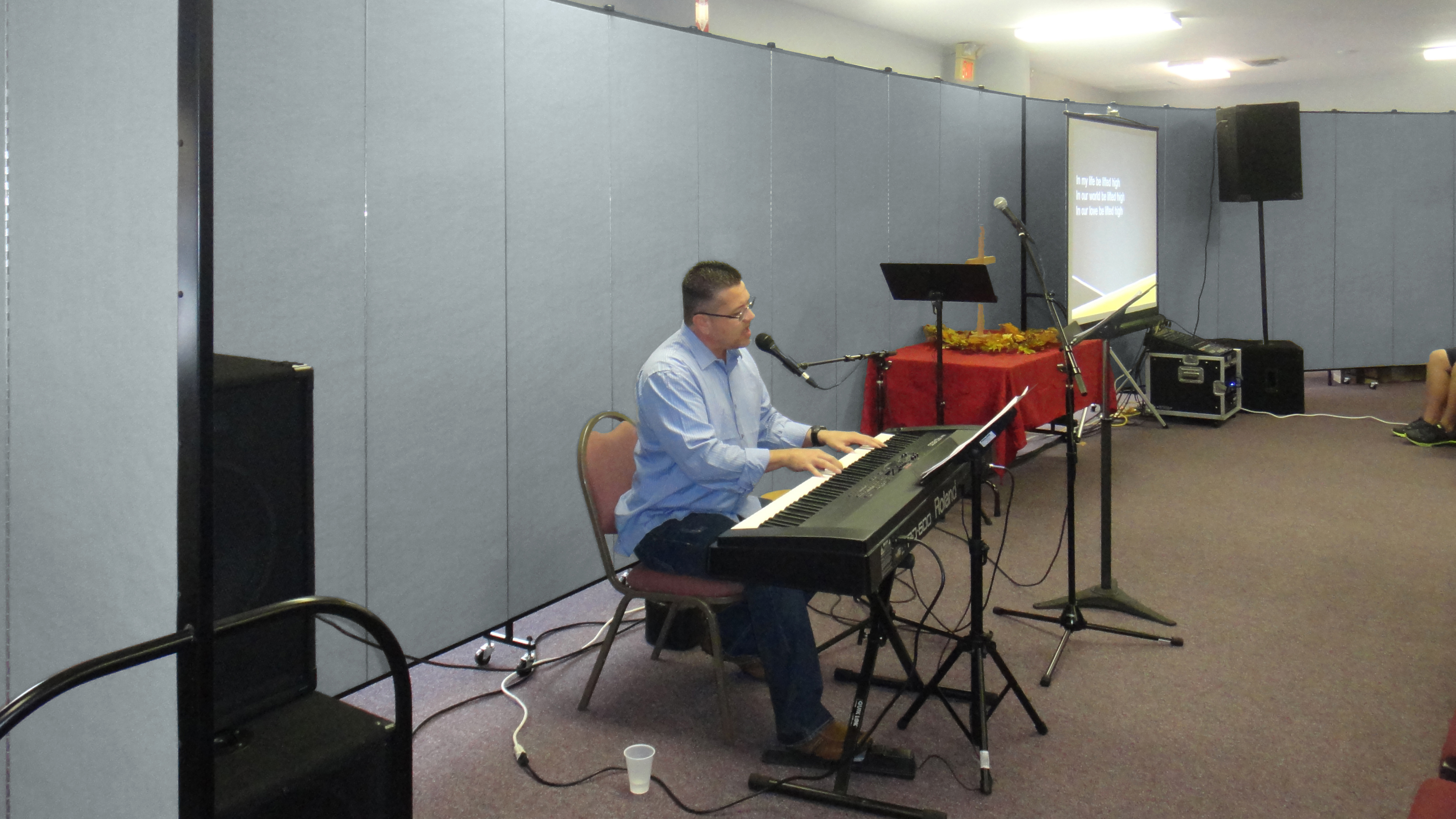 Room Dividers surround a church worship pastor leading song an praise from behind a keyboard