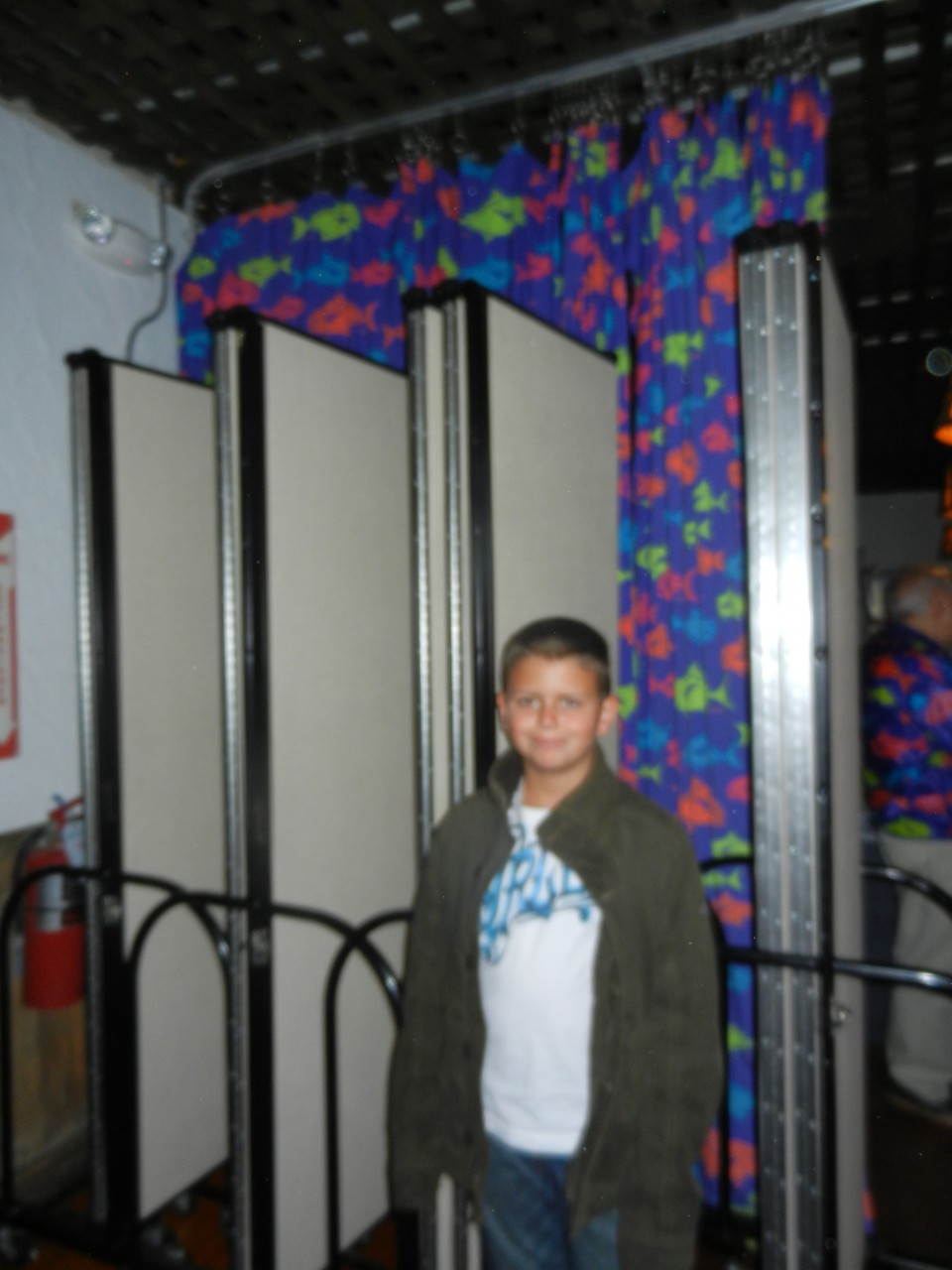 A teen boy stands in front of 4 closed room dividers
