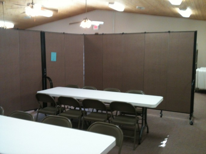 A set room dividers partially surrounds two rectangular tables and chairs in a larger room