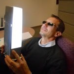 "A man in shades holds a ""happy light"" to his face"