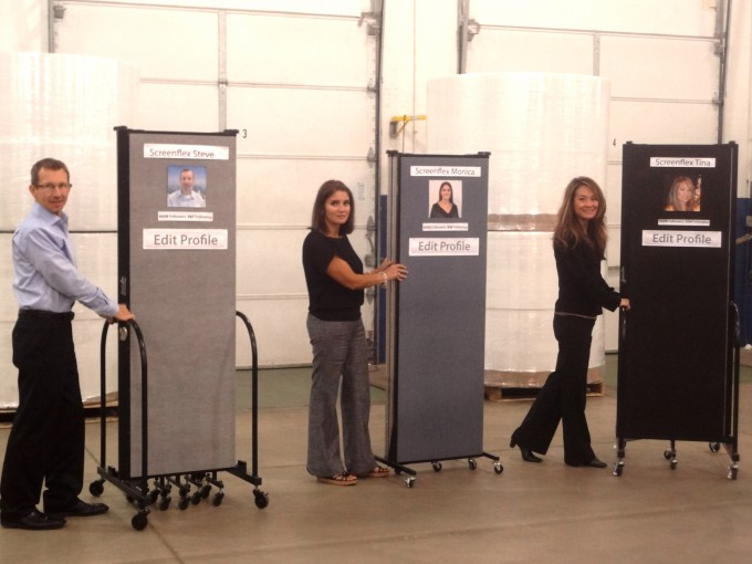 A man and two women each stand next to a Screenflex Portable Room Divider