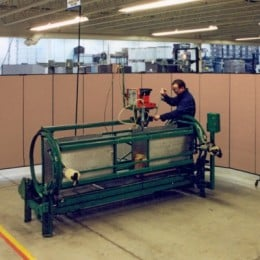 A Screenflex Room Divider creates a safety barrier around a man working on heavy machinery