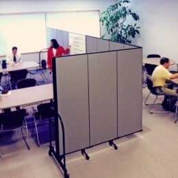 A cafeteria is divided into meeting and eating space with a Screenflex Room Divider