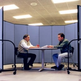 A Screenflex Room Divider is arranged in a circle around two men sitting at a round table