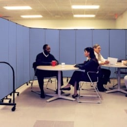 Four employees sit at two round tables in a cafeteria