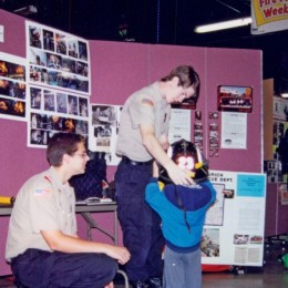 A Boy Scout places a fire helmet on the head of a young boy who is visiting the fire prevention booth