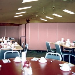 A hall is separated into dining and meeting area with a row of Screenflex Room Dividers