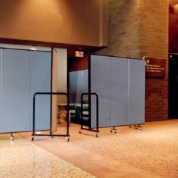 A Screenflex Room Divider creates a meeting room in a hotel lobby during a busy convention.
